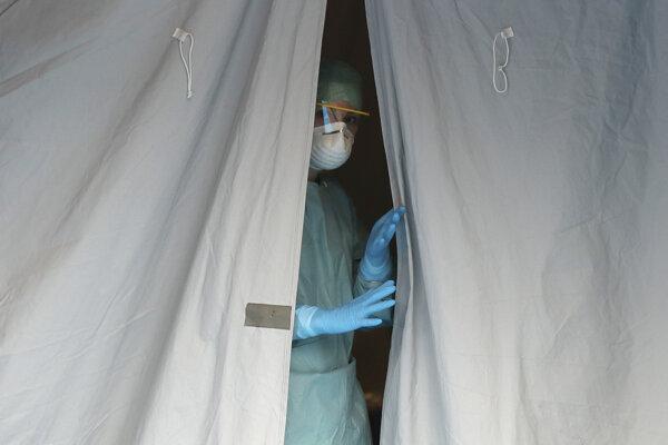 Zdravotníčka sa pozerá z jedného zo stanov pred nemocnicou v talianskom meste Brescia.