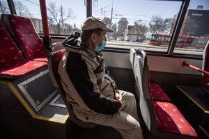 Cestujúci v autobuse s rúškom na tvári ako opatrenie v súvislosti s výskytom ochorenia COVID-19.
