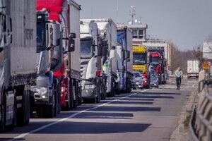 Muž na skútri prechádza okolo nákladných áut stojacich na diaľnici na hranici Nemecka s Francúzskom v meste Rheinau.