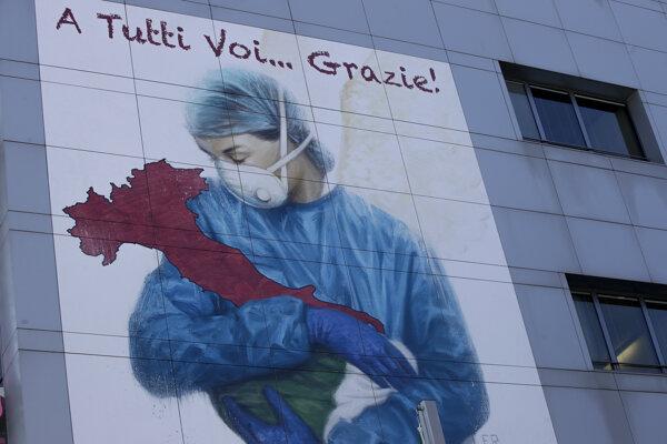 """Kresba v nadrozmernej veľkosti, ktorá zobrazuje zdravotnú pracovníčku s ochranným rúškom na tvári objímajúcu čižmu v tvare Talianska a nápis """"Ďakujeme vám všetkým"""", sa nachádza na budove nemocnice v severotalianskom meste Brescia."""