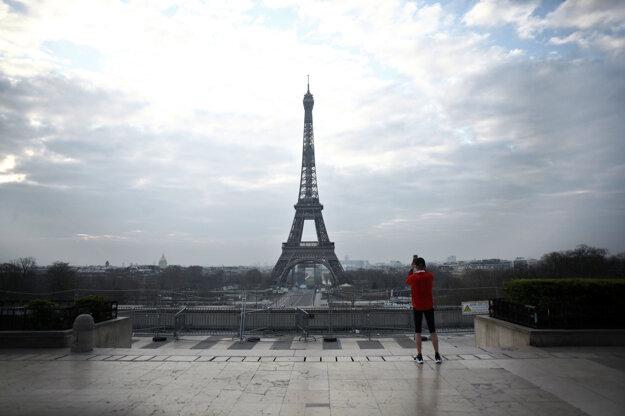 Muž si fotografuje Eiffelovu vežu v Paríži.