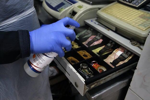 Muž dezinfikuje bankovky v pokladni v rámci preventívnych opatrení proti šíreniu nového koronavírusu v Bejrúte.
