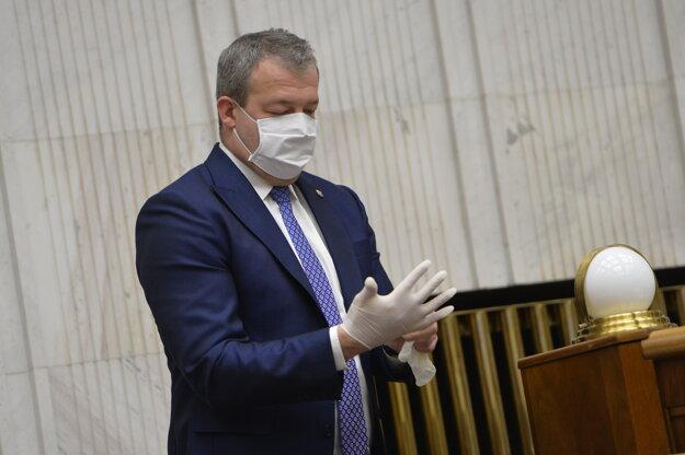 Jaroslav Baška (SMER) s ochranným rúškom na tvári si dáva ochranné rukavice