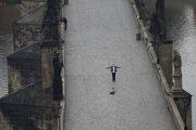 Muž si robí selfie na prázdnom Karlovom moste v Prahe.