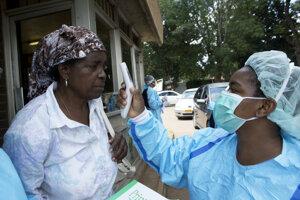 Zdravotníčka vyšetruje ženu v Harare.