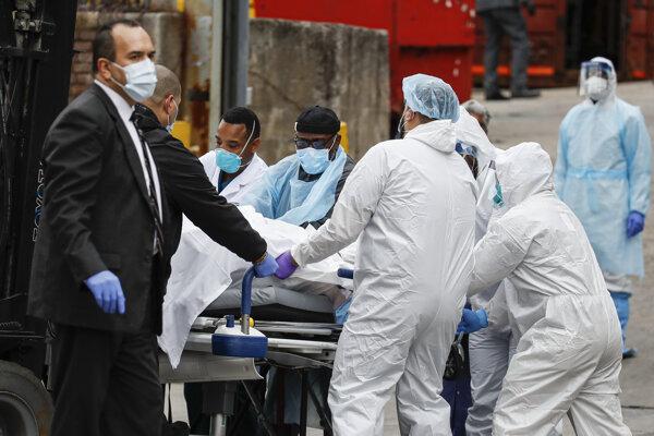 Zdravotníci tlačia na nosidlách telo obete zakryté prikrývkou v New Yorku.