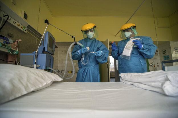 Členovia zdravotníckeho personálu kontrolujú ventilátor v ochranných oblekoch na jednotke intenzívnej starostlivosti v nemocnici v Budapešti.