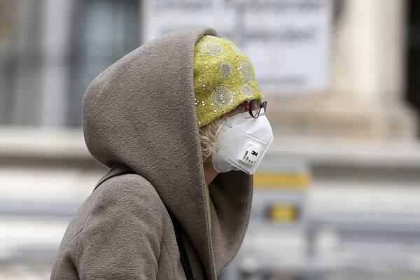 Žena s respirátorom na tvári kráča ulicou vo Viedni.