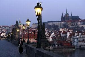 Žena s rúškom prechádza cez takmer prázdny Karlov most v Prahe.
