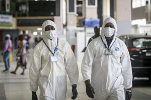 Zamestnanci nigérijských aerolínií v ochranných odevoch počas odletu amerických občanov domov spoločnosťou Delta Air Line na medzinárodnom letisku Muhammada Murtalu v Lagose v Nigérii 7. apríla 2020.