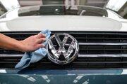 Na archívnej snímke z marca 2019 zamestnanec čistí na aute logo Volkswagen v Hannoveri.