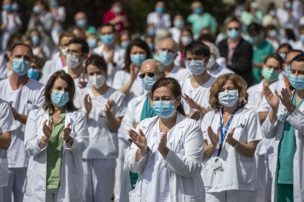 Zdravotníci tlieskajú počas minúty ticha na počesť Joaquina Diaza, hlavného chirurga nemocnice, ktorý zomrel na COVID-19 v nemocnici La Paz v Madride.