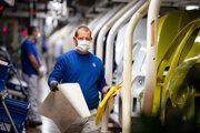 Zamestnanec s rúškom na tvári chodí po výrobnej hale v najväčšom závode nemeckej automobilky Volkswagen, ktorý obnovil výrobu po koronavírusovej odstávke v meste Wolfsburg.