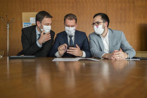 Zľava minister financií Eduard Heger (OĽaNO), premiér Igor Matovič (OĽaNO)  a vedúci Úradu vlády Július Jakab čakajú na brífing v tlačovej miestnosti pre novinárov na Úrade vlády 30. apríla 2020 v Bratislave.