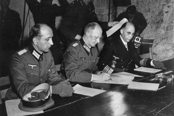 Na archívnej snímke zo 7. mája 1945 zástupca nemeckých ozbrojených síl  generálplukovník Alfred Jodl (uprostred) podpisuje protokol o bezpodmienečnej kapitulácii Nemecka v II. svetovej vojne vo francúzskom Remeši.