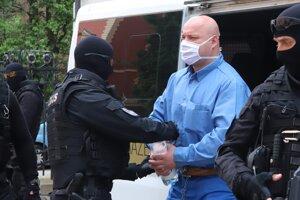 Eskorta privádza strelca Štefana Kaluza, právoplatne odsúdeného na 25 rokov basy v prípade vraždy exprimátora Hurbanova Lászlóa Basternáka, do budovy Špecializovaného trestného súdu v Banskej Bystrici.