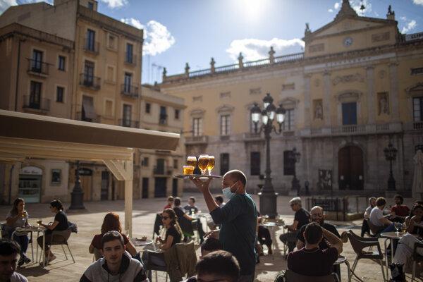 Čašník nesie pivo pre zákazníkov na terase v španielskej Tarragone.