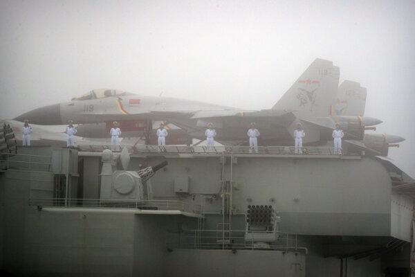 Na snímke z apríla 2019 námorníci stoja blízko bojových lietadiel na palube lietadlovej lode Čínskej ľudovej oslobodzovacej armády počas prehliadky v mori pri Čching-tao v provincii Šan-tung na východe Číny.