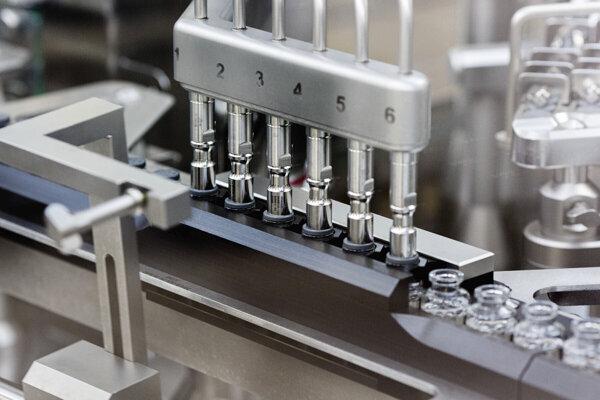 Na snímke z marca 2020 vidno napĺňanie flaštičiek liekom remdesivir vo výrobnom závode spoločnosti Gilead.