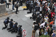 Policajti na znak solidarity pokľakli pred demonštrantmi.