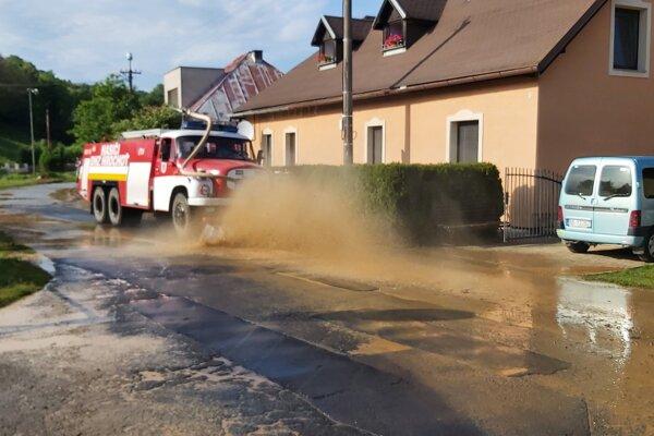 Dobrovoľní hasiči z neďalekej Hrochote prišli čistiť komunikáciu, ktorá bola zanesená nánosmi bahna.