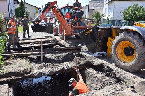 Oprava zničenej cesty v obci Pichne.