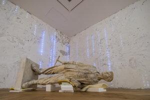 Povalená socha v štýle socialistického realizmu pri vstupe do výstavy Generácia 909,76 v SNG.