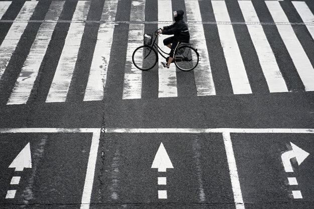 Koronavírus vo svete: Cyklista s ochranným rúškom prechádza cez prechod pre chodcov v Tokiu v stredu 15. júla 2020