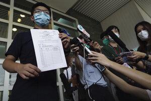 Hongkonský aktivista Joshua Wong s oficiálnymi dokumentmi, ktoré mu umožnia kandidovať v septembrových voľbách do Legislatívnej rady Hongkongu.