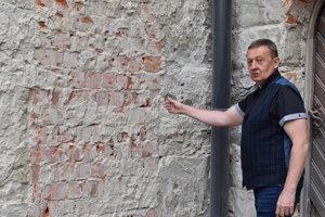 Vasil Fedič ukazuje zamurované dvere.