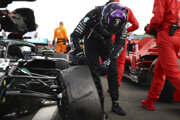 Lewis Hamilton si obzerá zničenú pneumatiku.