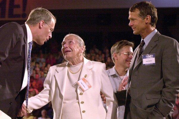 Na archívnej snímke z 1. júna 2001 syn zakladateľa Wal-Mart Stores Inc. John Walton stojí vedľa svojej matky Helen Walton (uprostred) a brata Roba Waltona (vľavo) tlieska na stretnutí akcionárov Wal-Martu vo Fayetteville.