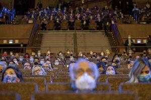 Hostia sedia s ochrannými rúškami počas otváracieho ceremoniálu.