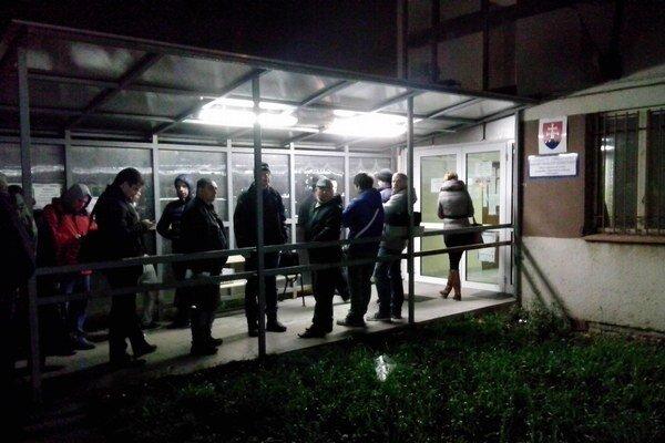 Ľudia čakajú skoro ráno pred vchodom do priestorov dopravného inšpektorátu v Bratislave.