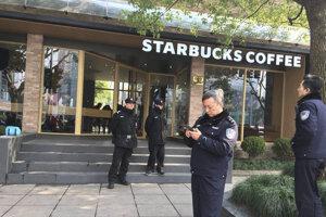 Policajti stoja pred kaviarňou Starbucks v Šanghaji.