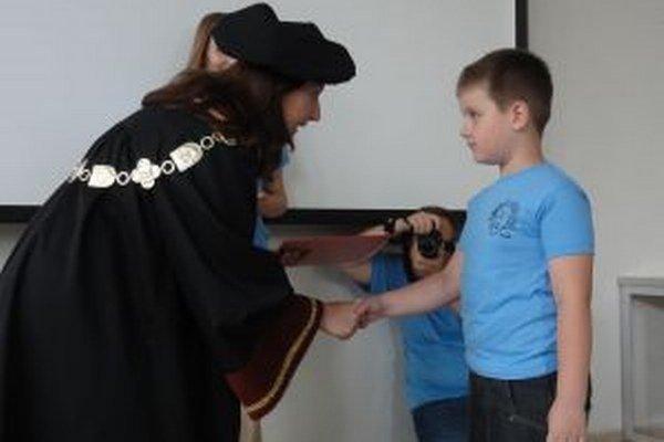Prorektorka UKF Miroslava Líšková odovzdáva diplom jednému zo škôlkárov.