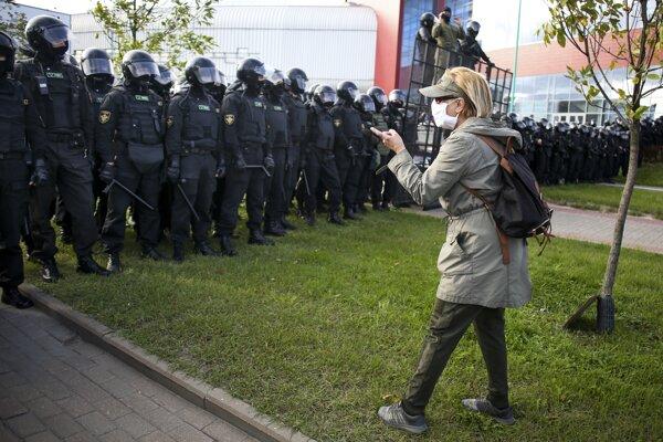 Žena gestikuluje pred príslušníkmi polície počas protestu v Minsku.