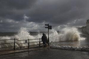 Ľudia sledujú, ako sa vlny rútia pozdĺž pobrežia vo Swanage v anglickom Dorsete v piatok 2. októbra 2020. Časti Spojeného kráľovstva sa pripravujú na búrku Alex, ktorá cez víkend ohlasuje príchod nepriaznivého počasia.