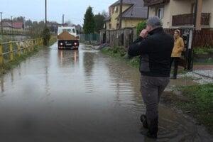 Voda zaliala aj cestu, ohrozuje domy.