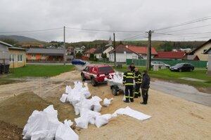 Dobrovoľní hasiči vrecujú piesok pre ľudí.