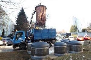 Kontajnery vyprázdňujú pomocou hydraulickej ruky.