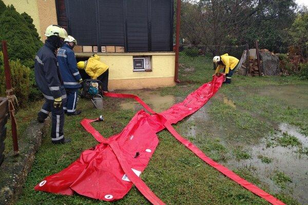 Dobrovoľní hasiči pri príprave mobilnej zábrany vo Veľkých Dravciach.