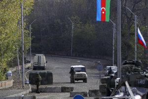 Azerbajdžanský vojak (uprostred) stojí pred konvojom ruských vojenských vozidiel na kontrolnom stanovišti na ceste do azerbajdžanského mesta Šuša v Náhornom Karabachu.