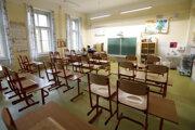 Učiteľka sedí v prázdnej triede a pripravuje si materiály pre žiakov počas dištančnej výučby.