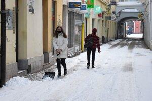 Žena odhŕňa sneh na jednej z ulíc v centre Košíc.