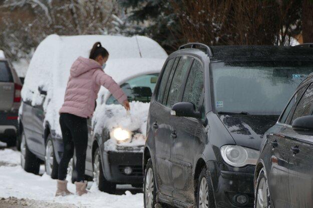 Žena odhŕňa sneh z auta na žilinskom sídlisku Vlčince.