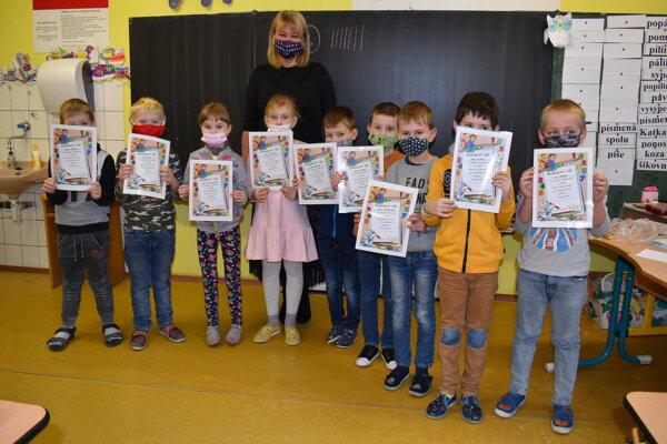 Najväčšiu radosť z prvého vysvedčenia mali prváci. Na snímke s riaditeľkou ZŠ Kudlovská Paulínou Škerlíkovou.