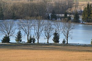 Lavičky a stromy pri rybníku ponúkajú príjemný oddych.