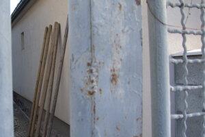 Pohľad na poškodenú fasádu spoza susedovho plota.
