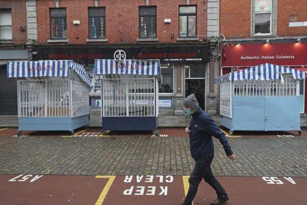 Muž s ochranným rúškom kráča po prázdnej ulici 20. októbra 2020 v Dubline.